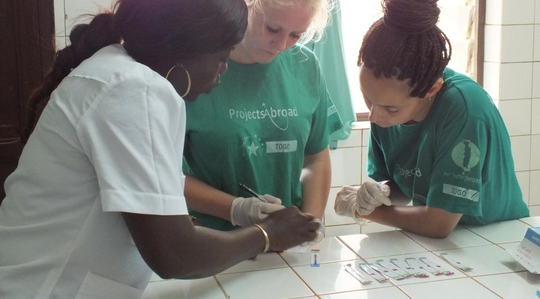 En un voluntariado para jóvenes, una doctora enseña a dos voluntarias a realizar pruebas.